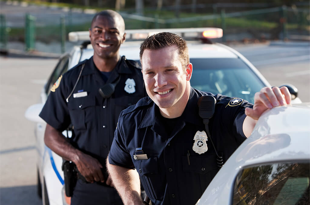 Two police officers standing and smiling in front of their patrol car